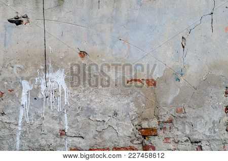 Old Grey Concrete Garage Wall With Red Bricks, Cracks And White Spots Abstract Background