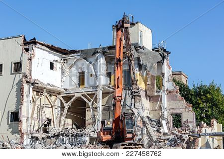 Bulldozer Removes The Debris From Demolition Of Old Industrial Building
