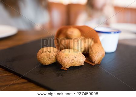 Close Up Croquettes In Paper Cornet On Black Tray