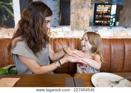 Happy Girl And Mother In Restaurant Playing With Hands