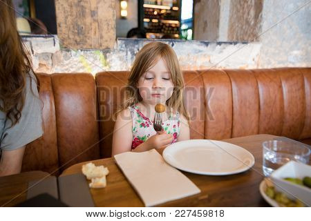 Little Girl Looking At Croquette In Fork At Restaurant