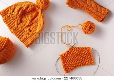 Knitted yarn, hat and mittens on a white background, top view