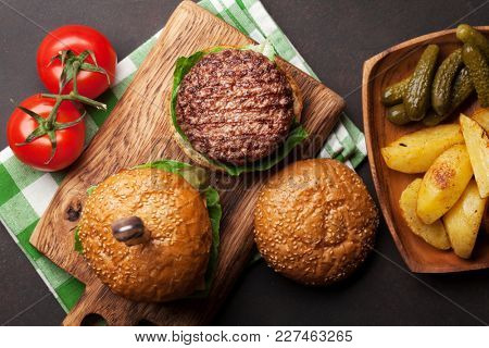 Tasty grilled home made burgers with beef, tomato, cheese, cucumber and lettuce. Top view