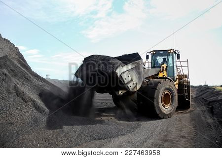 Front-end Loader Scooping Up A Pile Of Mining Ore Dust For Processing