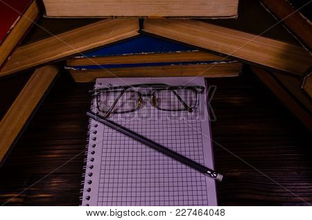 Notepad, Eyeglasses And Pencil In Front Of Many Books