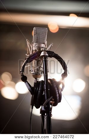 Headphones Hanging On A Microphone Stand In A Back-lit Recording Studio