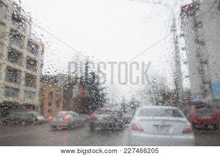 Street Bokeh Lights Out Of Focus. Rain Drops On Car Glass. Rainy Days, Blurry Car Silhouette