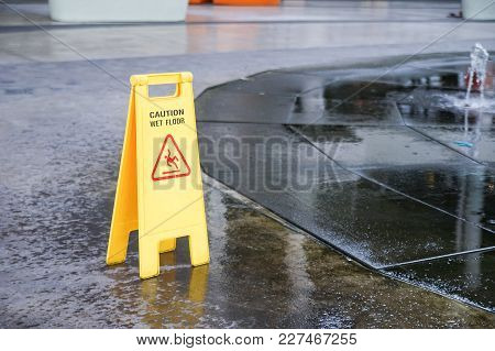 Caution Wet Floor Warning Sign Near Wet Area With Blurred Background