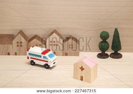 Miniature Houses, Hospital And Ambulance On Wood. Emergency Transport Concept.