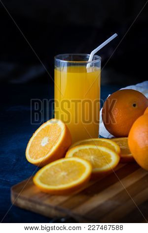A Glass Of Fresh Orange Juice With A Tube, A Wooden Cooking Table, Orange Slices, Oranges, White Clo