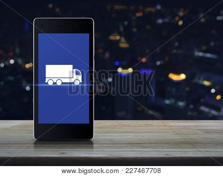 Truck Flat Icon On Modern Smart Phone Screen On Wooden Table Over Blur Colorful Night Light City Tow