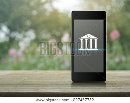 Bank Icon On Modern Smart Phone Screen On Wooden Table Over Blur Pink Flower And Tree, Mobile Bankin