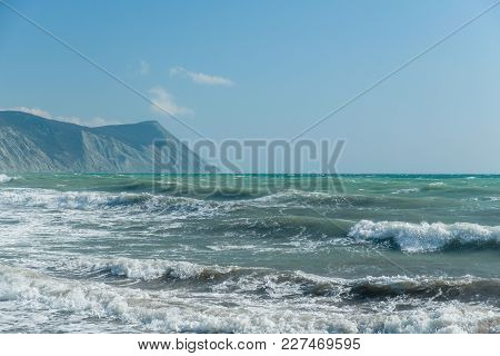Storm On The Stony Shore. Waves Rolling To The Shore. The Mountains In The Background.