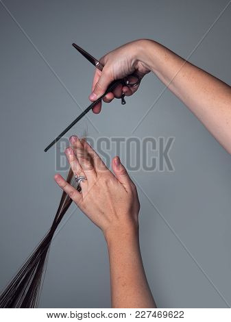 Stylist Measures With Comb And Hair Clippers For A Trim