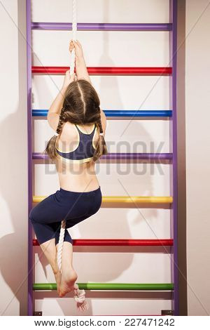 Little Caucasian 6-8 Years Old Girl Climbing A Rope, Multicolored Wall Mounted Gym Ladder In Backgro