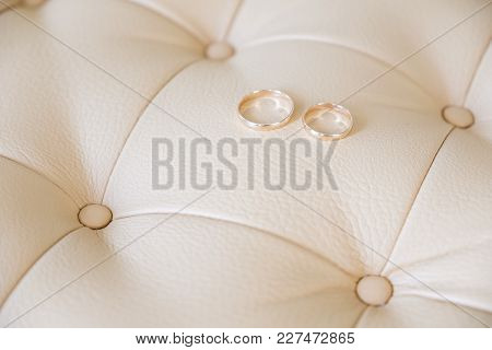 Wedding Rings On A Light Leather Sofa. Side View