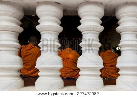 Three Monks In Orange Robes Behind Four Pillars