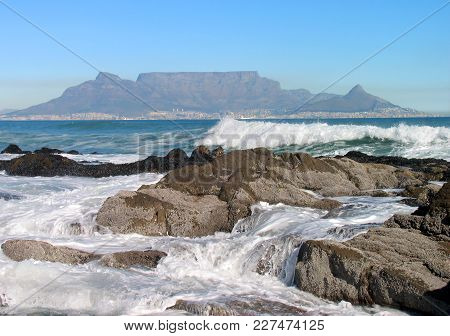 Seascape, With Some Waves Washing Over Some Rocks In The Fore Ground, And Table Mountain In The Back