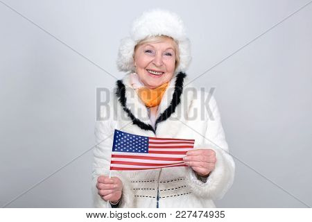 Senior Woman Holding A Flag Of The United States Of America. Adult Woman Is 70 Years Of Age. Old Fem