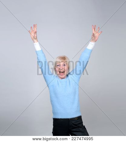 Adult Happy Woman Lifted Her Arms Up Over Her Head. Senior Woman 70 Years Of Age.