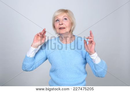 Senior Woman 70 Years Of Age. Woman Made A Wish And Crossed Her Fingers For Good Luck. Made A Wish.