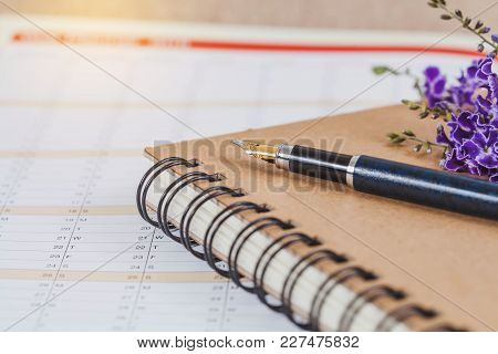 Personal Organizer Or Planner With Fountain Pen On Wood Table.