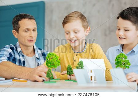 Vital Help. Charming Young Man Sitting At The Table Next To His Sons And Helping Them With Their Eco