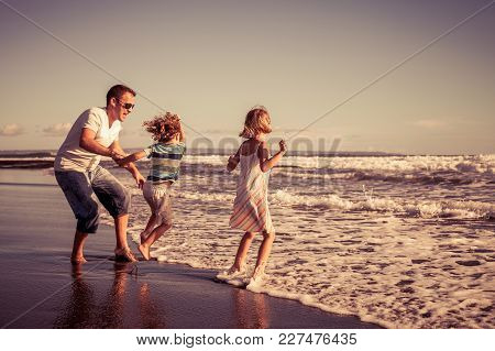 Father And Children Playing On The Beach At The Day Time. People Having Fun Outdoors. Concept Of Fri