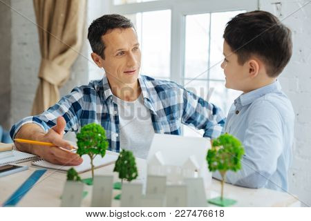 Want To Know More. Pleasant Pre-teen Boy Asking His Father About His Work As An Architect, Being Int
