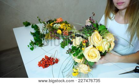 Young Charming Woman Loves Work And Holds Large Composition Of Flowers In Hands And Gently Corrects