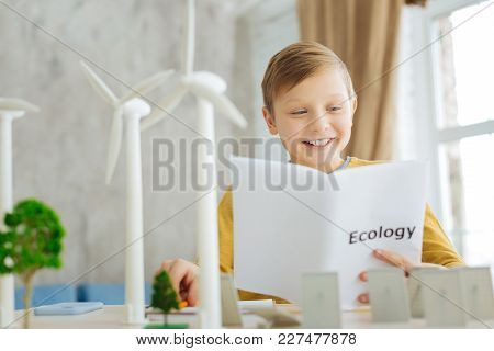 Young Researcher. Upbeat Pre-teen Boy Reading About Alternative Sources Of Energy In The Ecology Boo