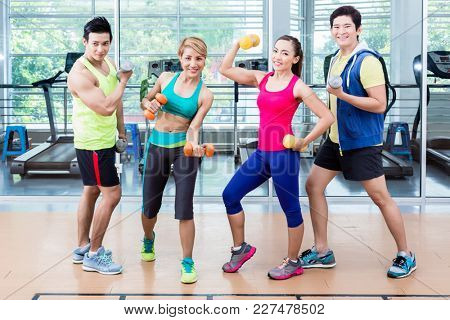 Sportsmen and sportswomen executing functional training routine with dumb-bells in gym