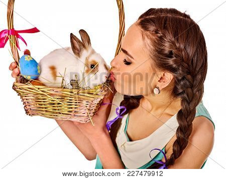 Easter girl holding bunny and eggs. Holiday style holding and group of rabbits in basket with flowers. Woman kiss rabbit on isolated. Care of animals.