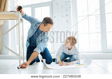 Best Cooperation. Pleasant Cheerful Young Father Measuring The Length Of The Table Leg And The Boy M