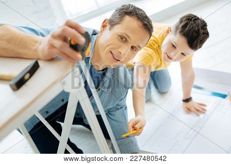 Willing To Help. Pleasant Pre-teen Boy Helping His Father To Measure The Table Leg By Checking The T
