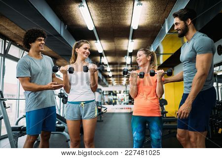 Young Beautiful Women Doing Exercises With Personal Trainers In Gym