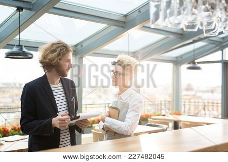 Young waitress listening to her employer during discussion of her working duties
