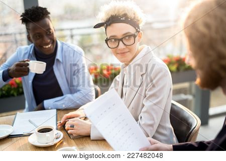 Young designer or manager listening to one of male colleagues during working conversation at meeting in cafe