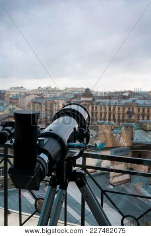 Black telescope on tripod in front of window with urban scene and grey sky outside