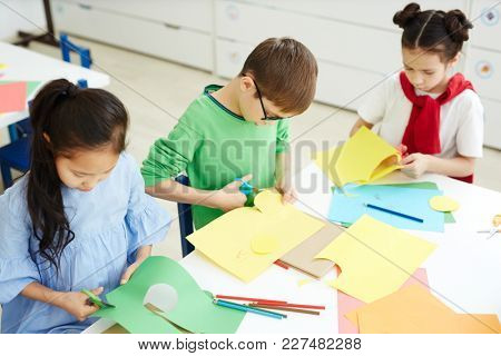 Group of scholars cutting various shapes from green and yellow paper at lesson