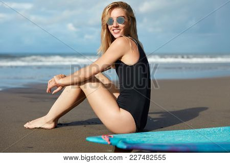 Happy Experienced Female Wears Bikini And Shades, Sits At Sandy Beach With Kite Board, Looks At Ocea