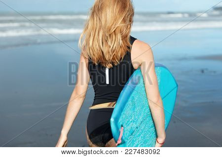 Unrecognizable Young Female Model Wears Bathing Suit, Has Long Light Hair, Stands Back To Camera, Ho