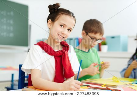 Smiling schoolgirl with colorful crayons looking at camera on background of schoolboy