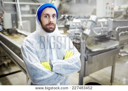 Fish factory staff in uniform crossing his arms on chest and looking at camera