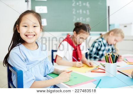 Cute schoolgirl with toothy smile looking at camera at drawing lesson on background of her classmates