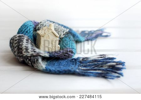 Stone House Wrapped In Blue Scarf On Light Background Front View / Warming Element For A Comfortable