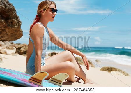 Outdoor View Of Adorable Female Model Dressed In Bathing Suit, Sits On Sandy Beach Alone, Rests With