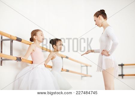 Professional ballet teacher talking to one of little ballerinas during training in classroom