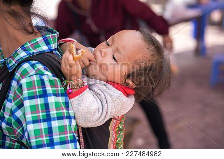 Lao Cai, Vietnam - Sep 7, 2017: Ethnic Minority Child On Her Mother Back At Local Market In Y Ty, Ba