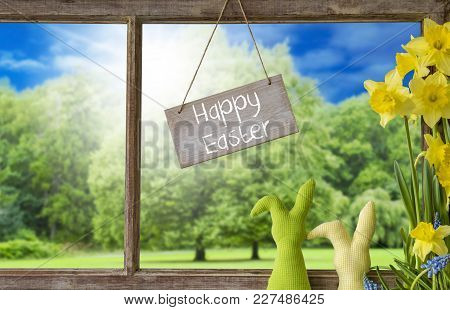 Sign With English Text Happy Easter. Window Frame With View To Beautiful Scenery Like Trees And Sunn